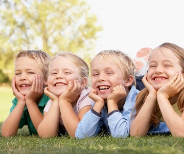 Four children laying in the grass smiling